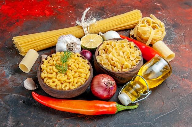 Close-up vista do frasco de óleo de massas crus e alimentos para a preparação do jantar na mesa de cores misturadas
