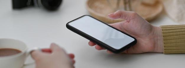 Close-up vista do freelancer feminino usando smartphone mock-up para entrar em contato com o cliente e beber café quente