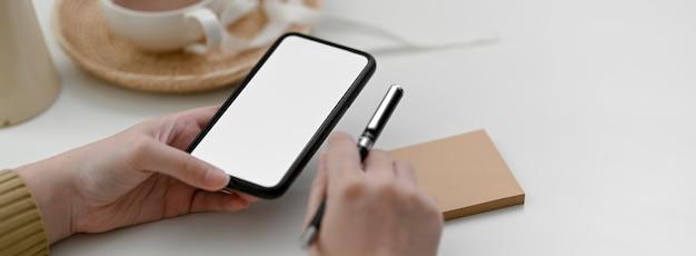 Close-up vista do freelancer feminino usando smartphone mock-up para entrar em contato com o cliente