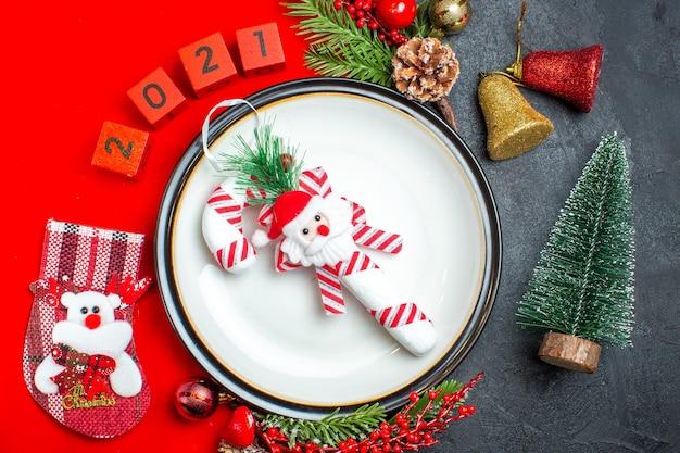 Close-up vista do fundo de ano novo com acessórios de decoração de prato de jantar ramos de abeto e números meia de natal em um guardanapo vermelho ao lado da árvore de natal em uma mesa preta
