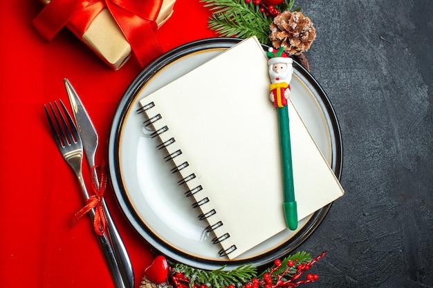 Close-up vista do fundo de ano novo com caderno espiral no prato de jantar talheres acessórios de decoração ramos de abeto ao lado de um presente em um guardanapo vermelho sobre uma mesa escura