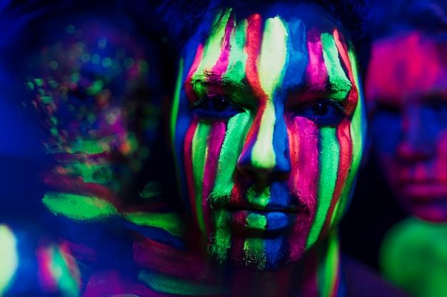 Close-up vista do homem com maquiagem fluorescente colorida