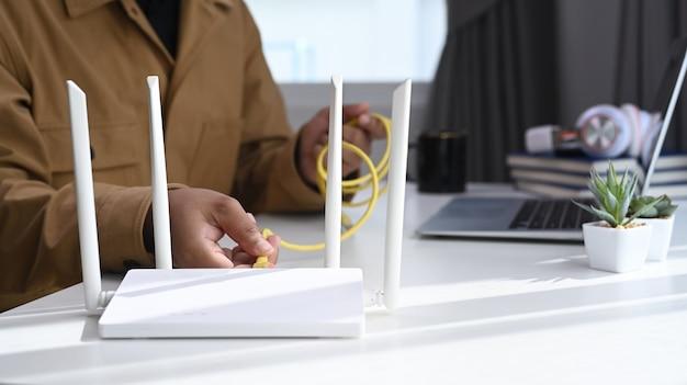 Close-up vista do homem conecta o cabo de internet ao roteador. conceito de internet sem fio.
