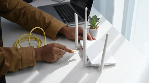 Close-up vista do homem conecta o cabo de internet ao soquete do roteador. conceito de internet sem fio.