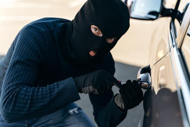 Close-up vista do homem perigoso vestido de preto com uma balaclava na cabeça arromba a fechadura com uma picareta enquanto rouba. ladrão de carros, conceito de roubo de carros