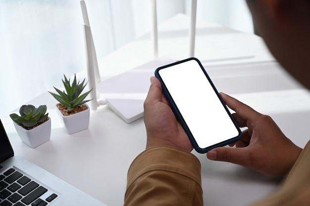 Close-up vista do homem usando o dispositivo de telefone inteligente para conectar a internet ou conexão sem fio em casa.