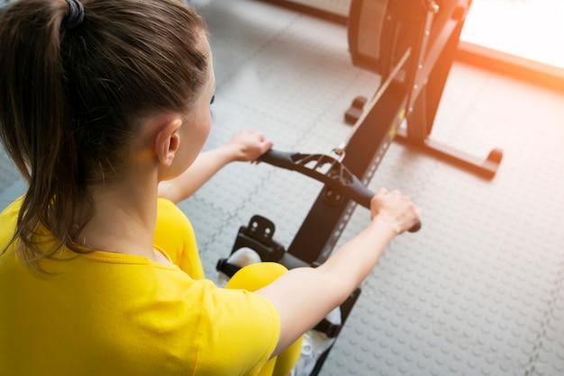 Close-up vista do instrutor de fitness feminino usa uma máquina de remo