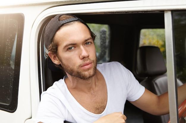 Close-up vista do jovem bonito com barba elegante, sentado no banco do motorista na cabine de couro de seu carro branco com tração nas quatro rodas e olhando com expressão séria durante a viagem