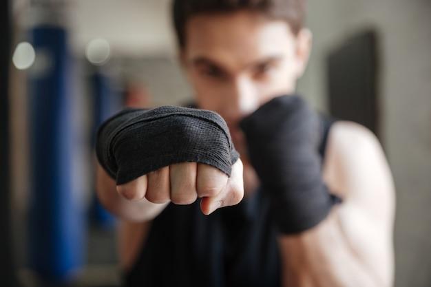 Close-up vista do jovem boxeador fazendo exercício no ginásio