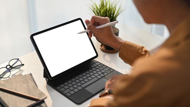 Close-up vista do jovem designer gráfico segurando a caneta stylus apontando na tela do tablet digital no escritório em casa.