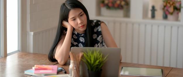 Close-up vista do jovem estudante feminino, sentindo-se tentado ao fazer lição de casa