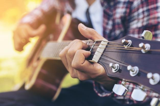 Close-up vista do jovem tocando violão.