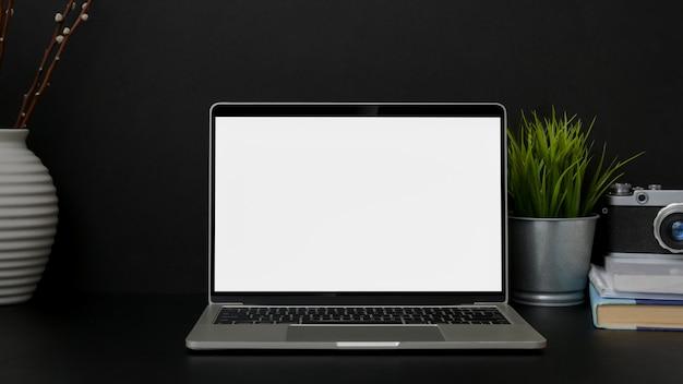 Close-up vista do local de trabalho de design de moda com laptop de tela em branco na mesa preta