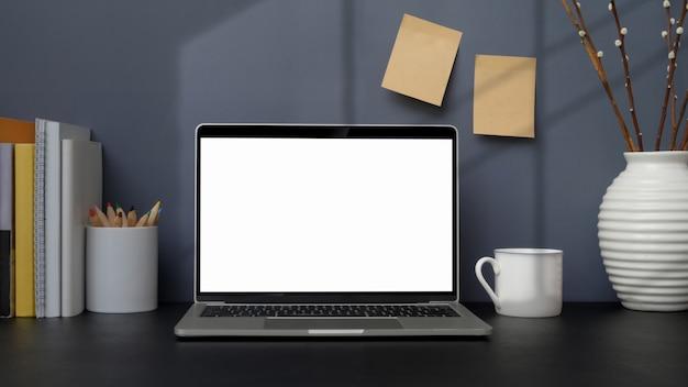 Close-up vista do local de trabalho moderno com laptop, livros e decorações