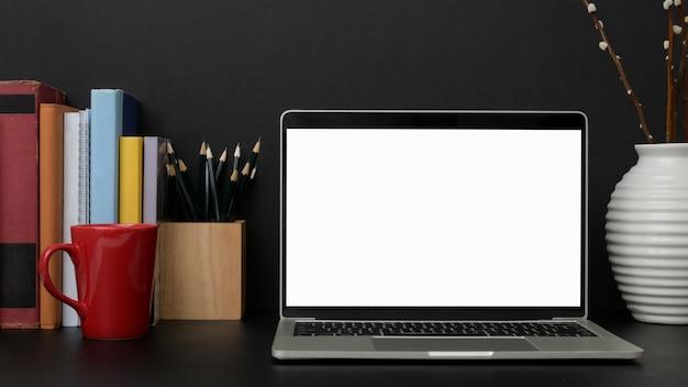 Close-up vista do local de trabalho moderno escuro com laptop de tela em branco na mesa preta