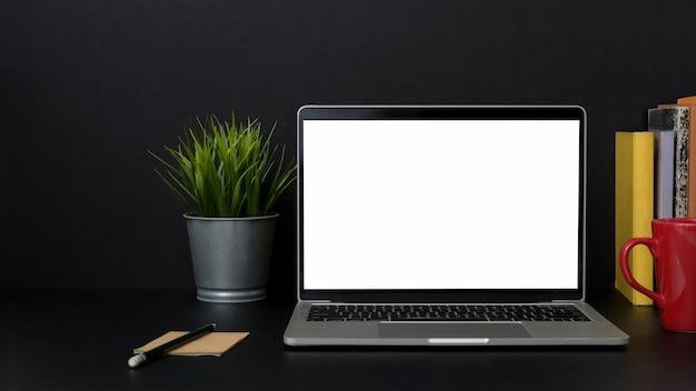 Close-up vista do local de trabalho moderno escuro com laptop na mesa preta