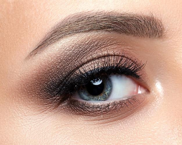 Close-up vista do olho azul da mulher com lindos tons dourados e maquiagem delineador preto. maquiagem clássica. sobrancelhas perfeitas.