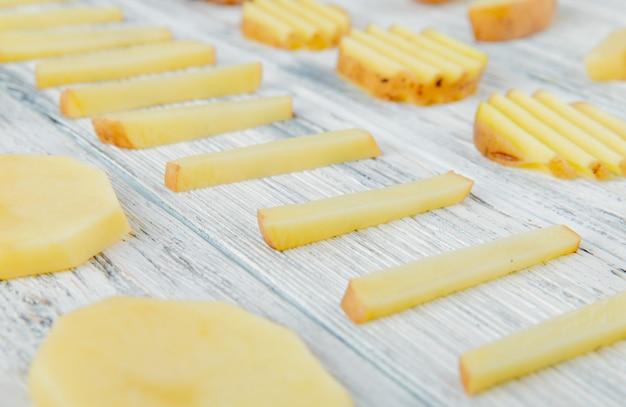 Close-up vista do padrão de batatas fatiadas no fundo de madeira