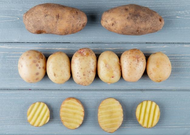 Close-up vista do padrão de batatas inteiras e fatiadas em fundo de madeira 2