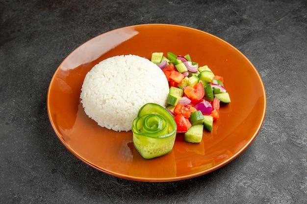 Close-up vista do prato de arroz caseiro e salada com tomate e pepino no escuro