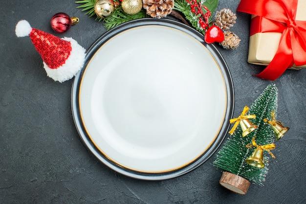 Close-up vista do prato de jantar árvore de natal galhos de pinheiro coníferas caixa de presente chapéu de papai noel em fundo preto