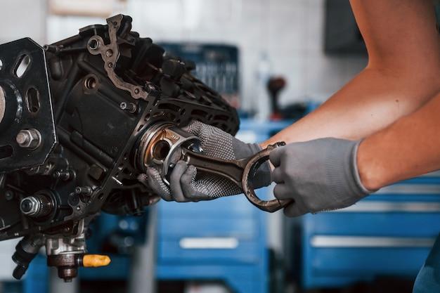 Close-up vista do reparador profissional na garagem que trabalha com motor de automóvel quebrado