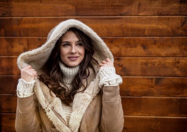 Close-up vista do retrato de com capuz satisfeito positivo elegante atraente linda jovem feliz no suéter e jaqueta olhando para longe, segurando o capuz com as mãos na frente da parede de madeira.