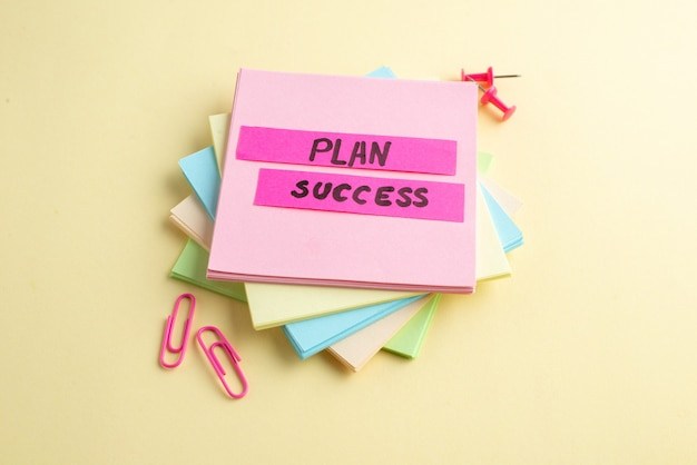 Close-up vista do sucesso do plano escrevendo em cubos de notas adesivas empilhadas e clipes de papel desenhando alfinetes em fundo amarelo com espaço livre