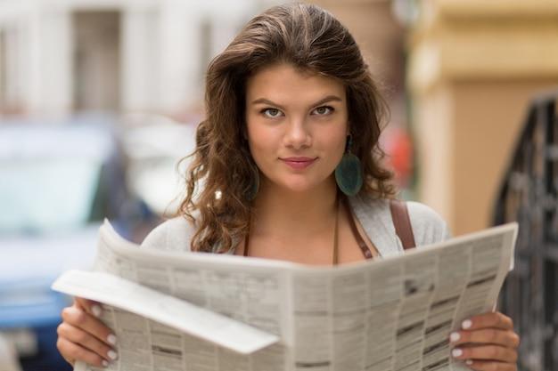 Close-up vista do turista garota segurando o jornal nas mãos dela.