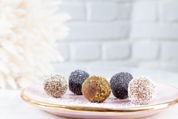 Close-up vista em conjunto diferente de cru, saudável, sem açúcar, doces veganos. bolos doces para o menu de dieta. doces sem glúten. bolas de doces crus. bolos de bola de energia na chapa rosa. configuração plana