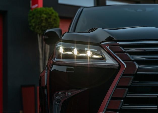 Close-up vista frontal do crossover moderno de cor preta faróis dianteiros iluminados do novo carro de luxo