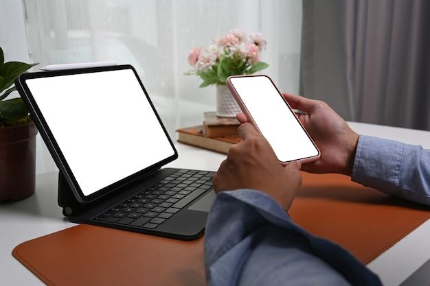 Close-up vista homem mãos segurando mock up telefone móvel com tela vazia.