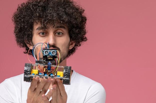 Close-up vista jovem olhando para a inovação do robô com cuidado