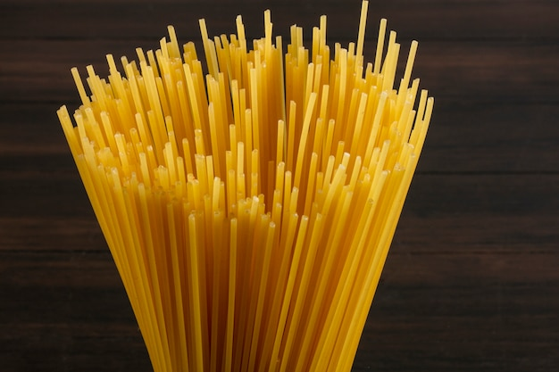 Close-up vista lateral de espaguete cru em uma superfície de madeira