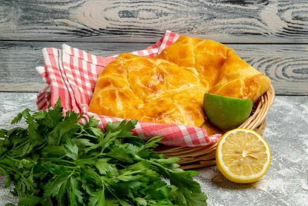 Close-up vista lateral de tortas e limões cesta de madeira de tortas apetitosas ervas limão e lima e toalha de mesa no fundo de madeira