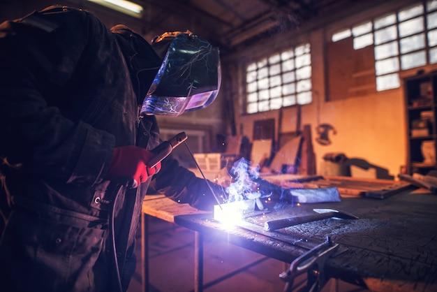 Close-up vista lateral do soldador profissional focado com máscara de proteção trabalhando com metal e faíscas em uma oficina de tecidos