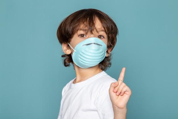 Close-up, vista menino bonitinho adorável em azul estéril máscara respiratória protetora na camiseta branca azul
