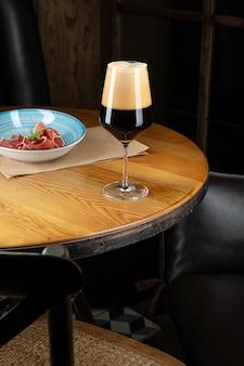 Close-up vista na cerveja artesanal escura escura em um copo com lanche no bar na mesa