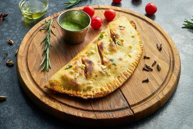 Close-up vista na pizza caseira e exuberante calzone com carne em uma bandeja de madeira e molho em uma superfície escura
