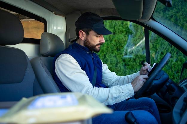 Close-up vista na remessa de pacotes e motorista de homem de entrega preenchendo papéis em sua van.