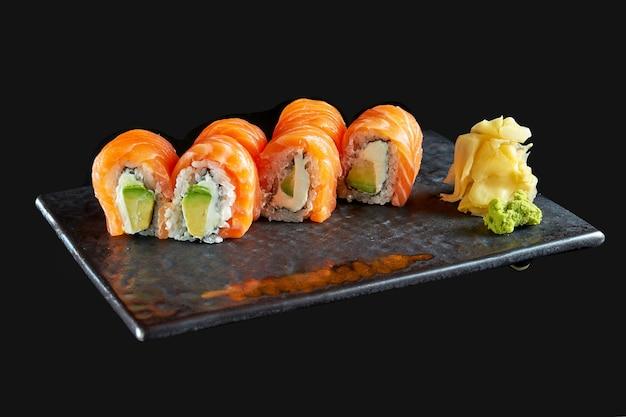 Close-up vista na saborosa filadélfia com salmão, abacate e caviar tobiko. cozinha tradicional japonesa. entrega de alimentos. isolado no preto