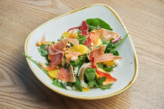 Close-up vista na saborosa salada leve com presunto, uma mistura de verduras, abacaxi e queijo azul em uma tigela cinza elegante.