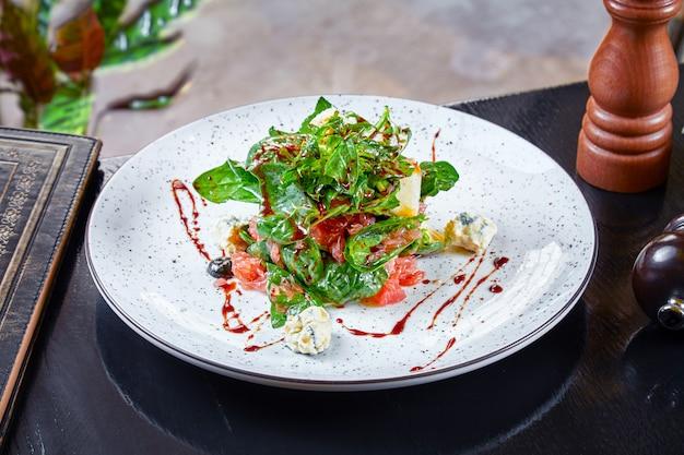 Close-up vista na salada com espinafre, queijo azul e toranja em fundo escuro. cozinha moderna. comida saudável para o almoço. dieta e equilíbrio alimentar. vista frontal. copie o espaço