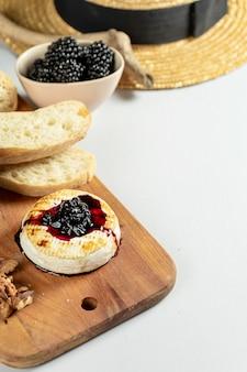 Close-up vista no camembert grelhado com geléia de amora, nozes e chiabatta em fundo cinza. copie o espaço. queijo. comida saborosa para o almoço. foco suave. alimento para o vinho