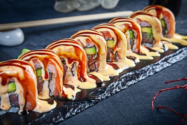 Close-up vista no conjunto de rolo de sushi. o rolo picante de califórnia com salmões serviu na pedra preta no fundo escuro. cozinha japonesa. copie o espaço. sushi servido no menu. comida saudável, frutos do mar