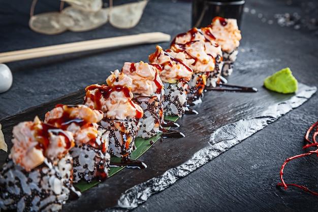 Close-up vista no conjunto de rolo de sushi. rolo com enguia e camarão servido na pedra preta sobre fundo escuro. cozinha japonesa. copie o espaço. sushi servido no menu. comida saudável, frutos do mar