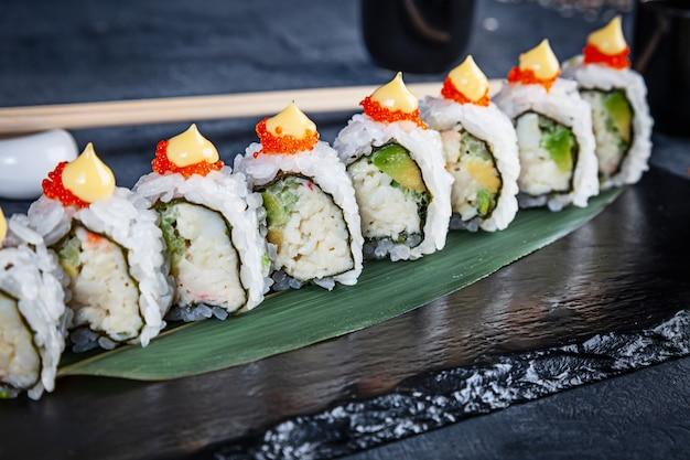 Close-up vista no conjunto de rolo de sushi. rolo de califórnia com caranguejo, abacate e caviar servido na pedra preta sobre fundo escuro. cozinha japonesa. copie o espaço. sushi servido no menu. comida saudável, frutos do mar