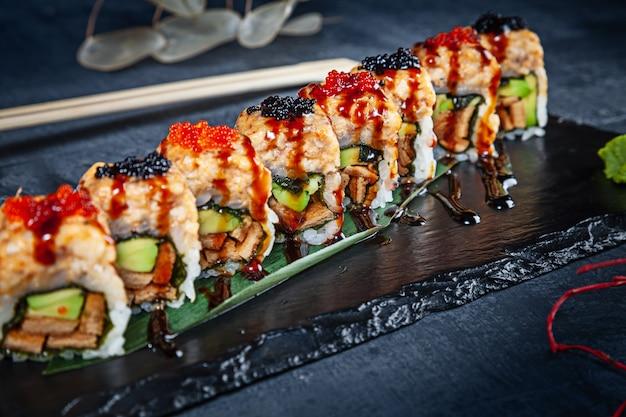 Close-up vista no conjunto de rolo de sushi. rolo picante com enguia, abacate e caviar servido na pedra preta sobre fundo escuro. cozinha japonesa. copie o espaço. sushi servido no menu. comida saudável, frutos do mar