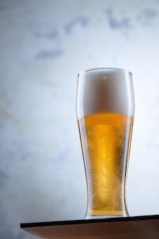 Close-up vista no copo de cerveja gelada fica na frente de um muro de concreto