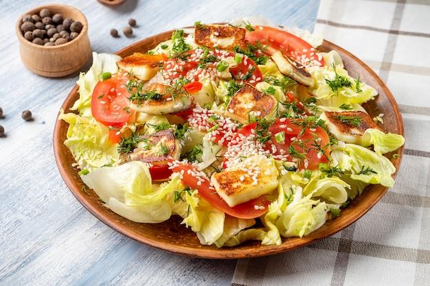 Close-up vista no prato grande com salada saborosa: tomate, queijo feta, queijo halumi, aspargos e verduras. fundo de foto de comida.